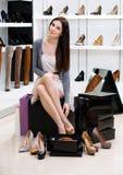 Kvinna som försöker på skor i shoppa Royaltyfri Fotografi