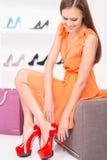 Kvinna som försöker röda skor som sitter i en shoppa Royaltyfri Foto