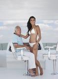 Kvinna som fabulerar med mannen på rodern av yachten fotografering för bildbyråer