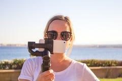 Kvinna som filmar solnedgång på loppet, video blogger som gör videoen med gimbalen och mobiltelefonen, solnedgångsjösidaplats royaltyfri bild