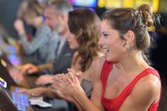 Kvinna som firar seger på enarmade banditen på kasinot arkivbilder
