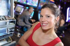 Kvinna som firar seger p? enarmade banditen p? kasinot royaltyfri foto