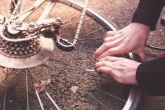 Kvinna som fixar hennes cykel Royaltyfri Foto