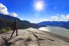 Kvinna som fotvandrar över överkanten av ett berg Arkivfoto