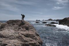 Kvinna som fotvandrar över stenblocket längs den Kalifornien kusten i den punktLobos delstatsparken - landskapriktning med kopier royaltyfri foto