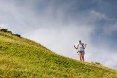 Kvinna som fotvandrar i berg med den stora ryggsäcken Arkivfoton