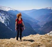Kvinna som fotvandrar in i bergen Arkivbilder