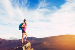 Kvinna som fotvandrar i bergen på solnedgången Arkivfoto