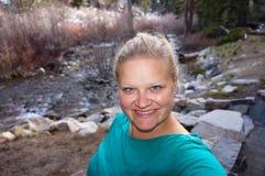 Kvinna som fotvandrar vid en ström Fotografering för Bildbyråer
