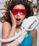 Kvinna som får laser-framsidabehandling i medicinsk brunnsortmitt Royaltyfria Foton