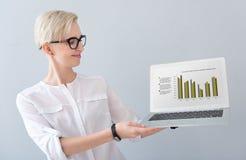 Kvinna som framlägger diagram på bärbara datorn royaltyfria foton