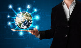 Kvinna som framlägger jordklotet för jord 3d i modern tablet Royaltyfri Bild
