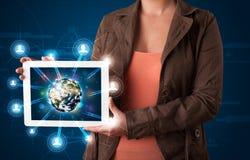 Kvinna som framlägger jordklotet för jord 3d i modern tablet Royaltyfria Bilder