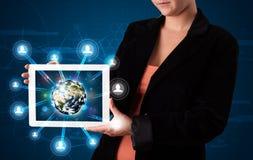 Kvinna som framlägger jordklotet för jord 3d i modern tablet Fotografering för Bildbyråer