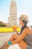 Kvinna som framme äter pizza av tornet av Pisa Fotografering för Bildbyråer