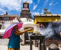 Kvinna som framme ber av den Bouddhanath stupaen Arkivfoton
