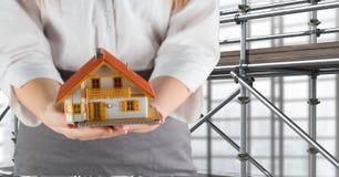 kvinna som framme ger ett hus av materialet till byggnadsställning 3D Arkivfoto
