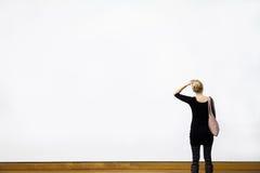 Kvinna som framme ifrågasätter av en tom vägg Arkivfoto