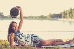 Kvinna som framme lägger i en äng av en sjö arkivfoto