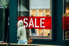 Kvinna som framme passerar av stort fönster av det lyxiga lagret Royaltyfri Fotografi