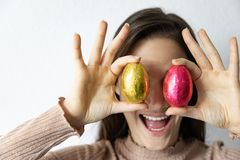 Kvinna som framme rymmer blåa och röda chokladeaster ägg av hennes ögon royaltyfri fotografi