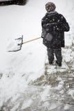 Kvinna som framme skyfflar snö från trottoaren av hans hus Arkivbild