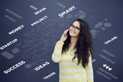 Kvinna som framme talar på telefonen av bakgrund med utdragna affärsdiagram Royaltyfri Foto