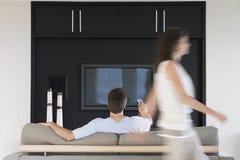 Kvinna som förbigår mannen som använder fjärrkontroll, medan hålla ögonen på TV Arkivfoton