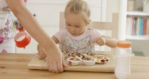 Kvinna som förlägger magasinet av det främsta barnet för muffin Arkivbilder