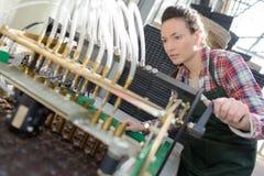 Kvinna som fungerar den industriella maskinen Arkivfoton