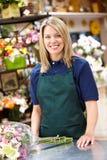 Kvinna som fungerar i blomsterhandlare fotografering för bildbyråer
