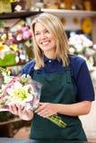 Kvinna som fungerar i blomsterhandlare Royaltyfria Foton