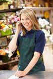Kvinna som fungerar i blomsterhandlare på telefonen Fotografering för Bildbyråer
