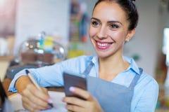 Kvinna som fungerar i coffee shop royaltyfri bild