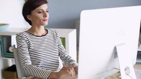 Kvinna som fungerar på datoren lager videofilmer