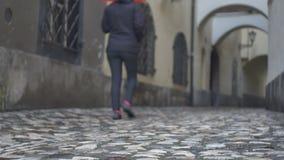 Kvinna som går över kullerstengränden stock video