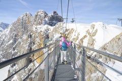Kvinna som går över repbron på det Dachstein berget royaltyfri foto