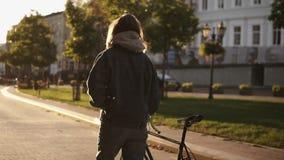 Kvinna som går bredvid ridningcykeln på stadsvägen Kvinnacykelryttare som går på stadsgatan Slut upp överblicken som skjutas av arkivfilmer