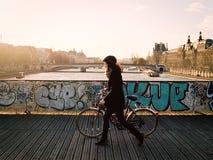 Kvinna som går cykeln över Pont des Arts på solnedgången Arkivfoto