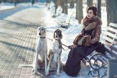 Kvinna som går en hund på gatan i vinter Arkivfoto