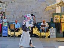 Kvinna som går förbi traditionella skoshiners arkivfoton