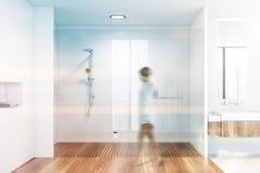 Kvinna som går i det vita badrummet, duschen och vasken arkivfoto