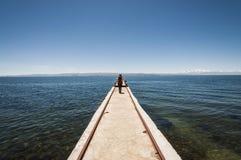 Kvinna som går i en kaj ovanför titicacasjön i en solig dag arkivfoto