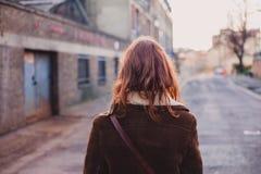 Kvinna som går i en stad i vintern Arkivfoto