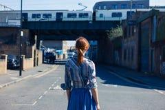 Kvinna som går i gatan nära trainline Royaltyfri Bild