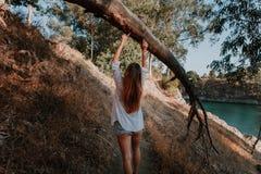 Kvinna som går i natur längs en bana som trycker på ett stupat träd med händerna Arkivbilder