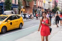 Kvinna som går i New York City genom att använda telefonen app Arkivbild
