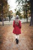 Kvinna som går i parkera i höst arkivfoto