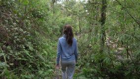 Kvinna som går i rainforest lager videofilmer
