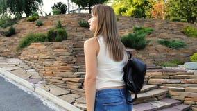 Kvinna som går i stenträdgården kvinnan med en kvinnlig ryggsäck går i parkera arkivfilmer